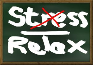 Chalkboard with the words stress and relax written on it. The word stres is crossed out with a red x.