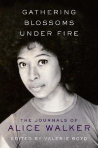 Gathering Blossoms Under Fire- The Journals of Alice Walker by Alice Walker book cover. Image on cover is of the author looking straight ahead with neutral expression on her face.