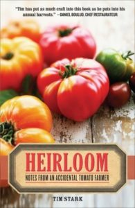 Heirloom- Notes from an Accidental Tomato Farmer by Tim Stark book cover. Image on cover is of green, purple, red, and orange heirloom tomatoes sitting on a wooden table.