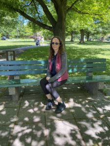 Woman sitting on a park bench underneath a large, shady tree.