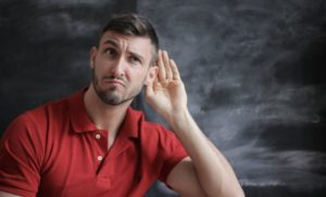 Man in red polo shirt sitting in front of chalkboard and holding his hand up to his ear as if to eavesdrop.
