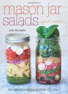 Mason Jar Salads and More- 50 Layered Lunches to Grab and Go  by Julia Mirabella book cover. Image on cover is of two mason jars filled with salad ingredients.