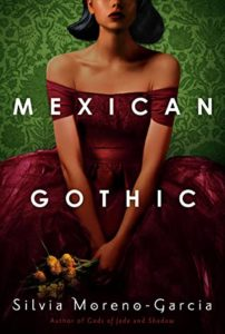 Mexican Gothic by Silvia Moreno-Garcia book cover. Image on cover is of a young girl wearing a red dress, clasping flowers, and sitting down.