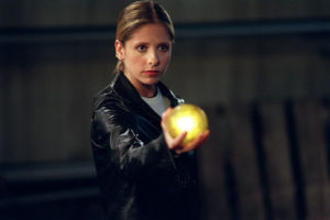 Sarah Michelle Gellar as Buffy Summers in Buffy the Vampire Slayer. She's holding a glowing orb.