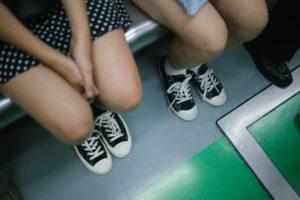 Shot of people's legs and feet as they sit on a bus