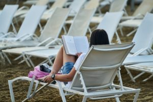 White woman reading a book while sitting in a lawn chair