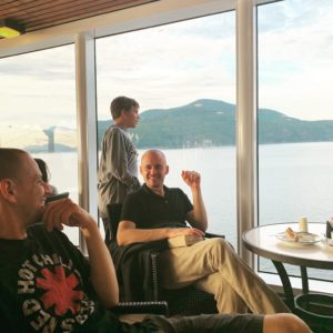 Two men and one preteen boy on the deck of a cruise ship smiling and talking.