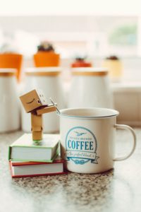 A cardboard robot standing on two stacked books while stirring a cup of coffee with a teaspoon