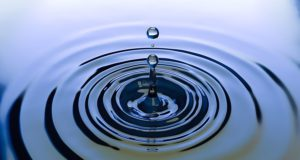 A drop of water falling into an otherwise still pool of water
