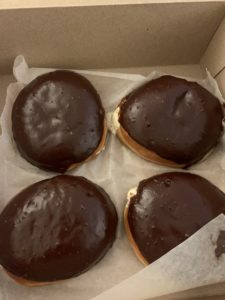 A cardboard box filled with four dairy-free boston creme donuts.