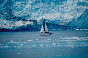 A small sailboat sailing next to a large glacier.