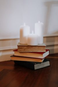Lit white candles on top of a stack of books.