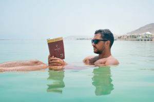 Man floating in a body of water while reading and wearing a pair of sunglasses