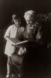 Senior woman sitting on chair while reading a book to a young girl