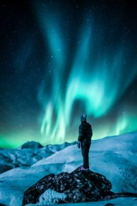 Person standing on snowy mountain while looking at aurora borealis at night