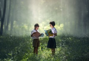 Two children standing in a forest reading books.