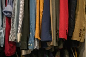 a closet filled with shirts and coats