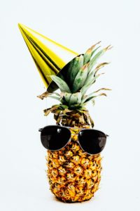 pineapple wearing sunglasses and a party hat