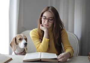 woman reading a book to her dog