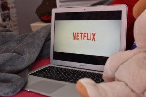 A laptop with the Netflix logo on it. The laptop is sitting on a bed and flanked by a stuffed animal and a blanket.