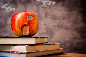 A toy apple sitting on three textbooks in front of a blackboard. The toy apple has a door, window, and lantern painted onto it so that it looks ilke a litle house.