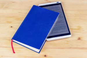 An ereader tucked inside of a hardback novel. The novel is sitting on a wooden surface, possibly a table or floor.