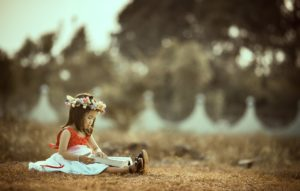 Child reading a book while sitting on brown grass and wearing a wreath of flowers in her hair outside