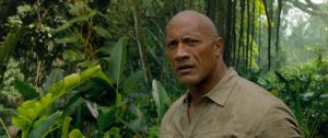 Dwayne Johnson as Dr. Xavier Smolder Bravestone. He's standing in a jungle.