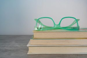 Green framed eyeglasses on top of a stack of three books