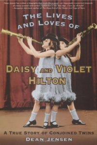The Lives and Loves of Daisy and Violet Hilton- A True Story of Conjoined Twins by Dean Jensen book cover. Image on cover is of Daisy and Violet playing instruments on a stage.