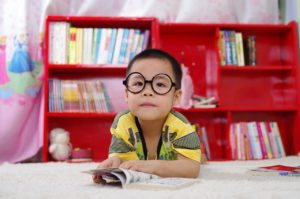 Young boy wearing black, Harry Potter style glasses reading a comic book