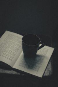 ceramic mug sitting on an opened book