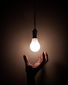 A hand reaching up to touch a bright lightbulb
