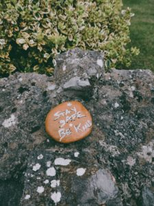 "A rock painted orange that says ""stay safe be kind."" It is lying on a much larger, lichen-covered rock."