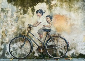 Bicycle leaning up against a mural of two children riding a bike so that it looks like they're riding a real bike