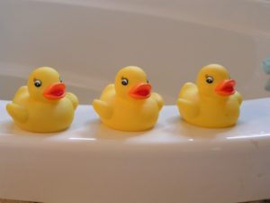 Three rubber duckies sitting on the edge of a white bathtub