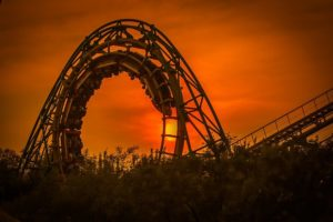 people riding a roller coaster at sunset
