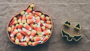 A pumpkin tin filled with candy corn. Tin cutouts of a pumpkin's eyes and mouth are sitting next to the candy on a linen tablecloth.