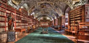 A shot of a beautiful monastary library in Prague. The ceilings have ornate paintings on them and the walls are lined with ornate wooden bookshelves filled with books.