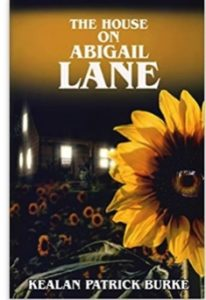 Book cover for The House on Abigail Lane by Kealan Patrick Burke. Image on cover is of a house that has all of its windows illuminated by light on a dark night. It is sitting next to a garden filled with sunflowers, one of which has a human-like eye in the centre of it staring straight ahead at the reader.