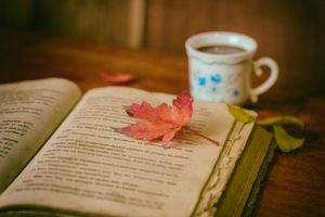 An autumn leaf lying on the page of an opened book. The book and a cup of coffee in the background are both sitting on a wooden table.