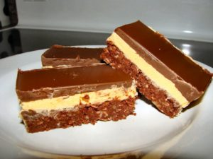 Nanaimo bars sitting on a white plate.
