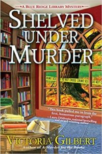 Shelved Under Murder (Blue Ridge Library Mysteries, #2)  by Victoria Gilbert book cover. Image on cover is taken from library looking out it's big picture window. There is a tree with a crime scene do not cross tape around it and many red, yellow, and orange leaves on the ground.