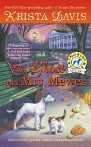 The Ghost and Mrs. Mewer (Paws and Claws Mystery, #2) by Krista Davis book cover. Image on cover is of a cat and dog looking at smashed halloween pumpkin on a residential driveway.