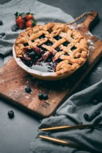 A blueberry pie sitting on a wooden cutting board