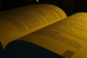 A close up photo of an opened book being illuminated by warm, yellow light.