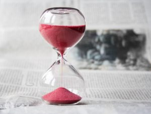 A closeup of pink sand in a glass hourglass