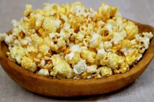 A wooden bowl filled with buttered popcorn