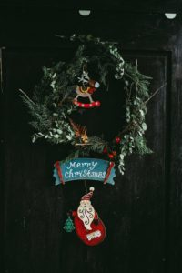 "Christmas wreath with a Santa placard saying ""Merry Christmas"" hung from it. The wreath is hung on a slightly ominious black door."