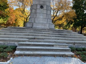 Close-up photo of World War I monument at a park. the monument is on a series of stone steps and surrounded by evergreen bushes.